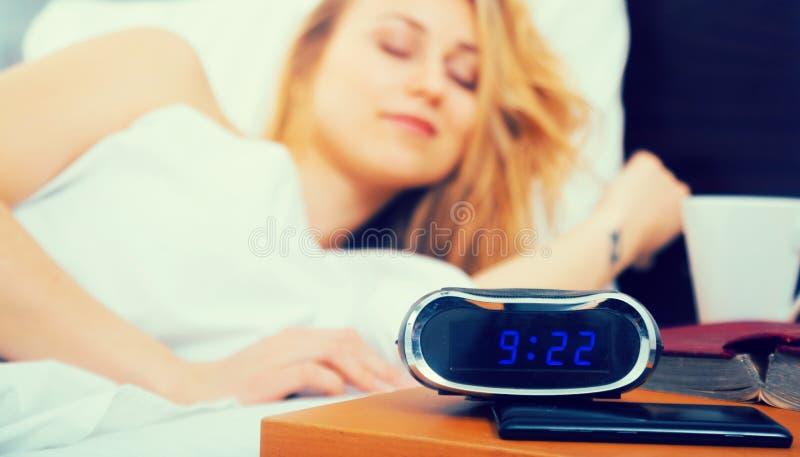 Ύπνος γυναικών κοντά στο ρολόι και το βιβλίο στοκ εικόνες με δικαίωμα ελεύθερης χρήσης