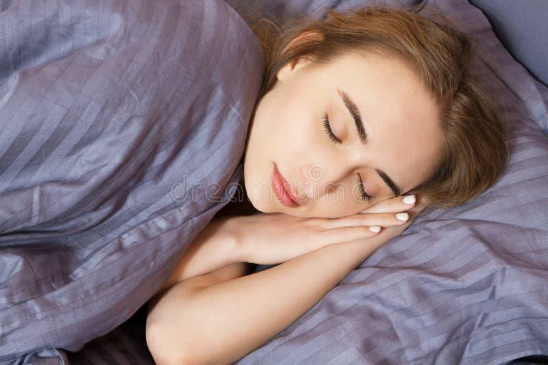 Ύπνος γυναικών στο κρεβάτι στη νύχτα, υγιής ύπνος, κρεβατοκάμαρα ύπνων κοριτσιών στοκ εικόνες
