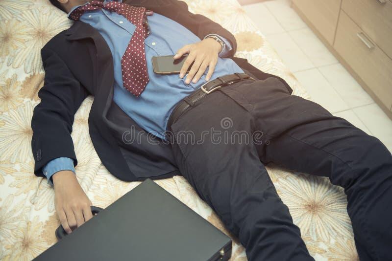 Ύπνος επιχειρηματιών κούρασης στο κοστούμι με την τσάντα και κινητός στο εκτάριο στοκ εικόνες