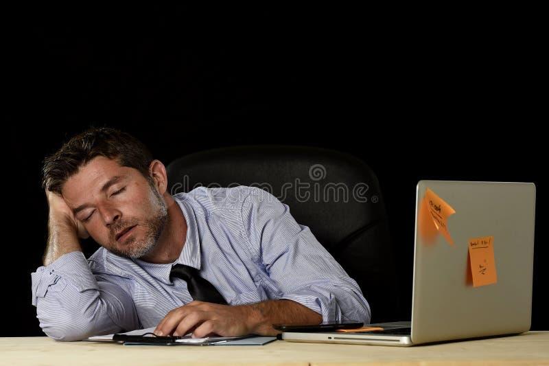 Ύπνος επιχειρηματιών που σπαταλιέται που κουράζεται στο γραφείο υπολογιστών γραφείων στις πολλές ώρες της εργασίας στοκ φωτογραφία