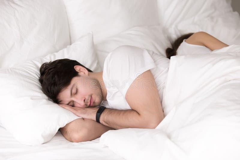Ύπνος ζεύγους ειρηνικά μαζί στο κρεβάτι, άτομο που φορά το έξυπνο wr στοκ φωτογραφίες