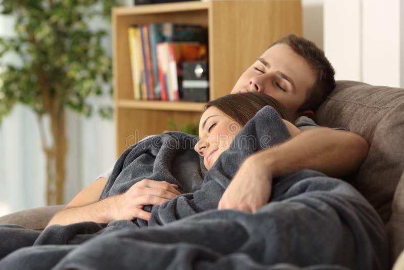 Ύπνος ζεύγους μαζί σε έναν καναπέ στο σπίτι στοκ εικόνα