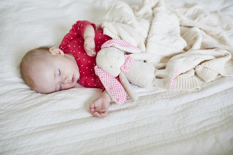 Ύπνος κοριτσάκι κάτω από το πλεκτό κάλυμμα με το αγαπημένο παιχνίδι της στοκ φωτογραφία