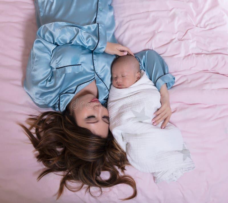 Ύπνος μητέρων και μωρών κοντά ενώ στο κρεβάτι στοκ φωτογραφία με δικαίωμα ελεύθερης χρήσης