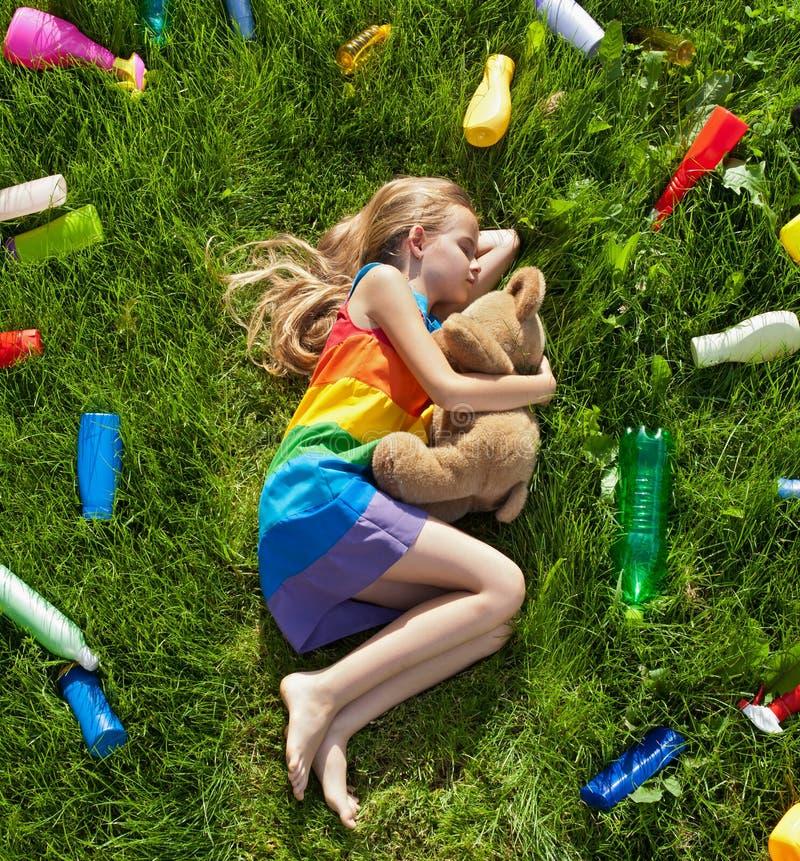 Ύπνος νέων κοριτσιών με τη teddy αρκούδα της στο πλαστικό που ρυπαίνεται στοκ εικόνες