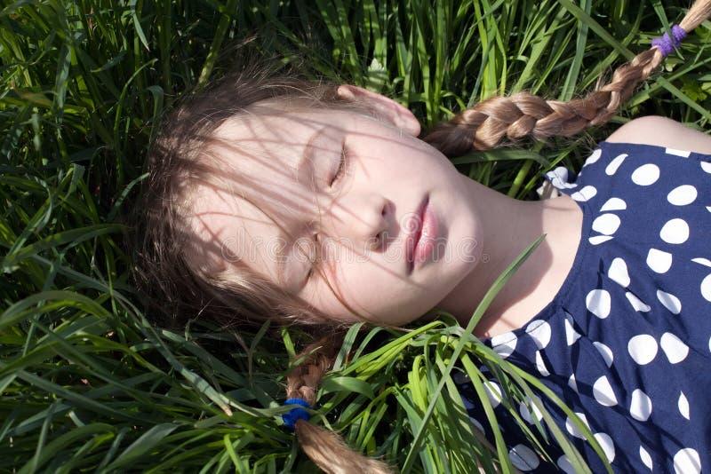 Ύπνος νέων κοριτσιών στην πράσινη χλόη στοκ φωτογραφίες με δικαίωμα ελεύθερης χρήσης
