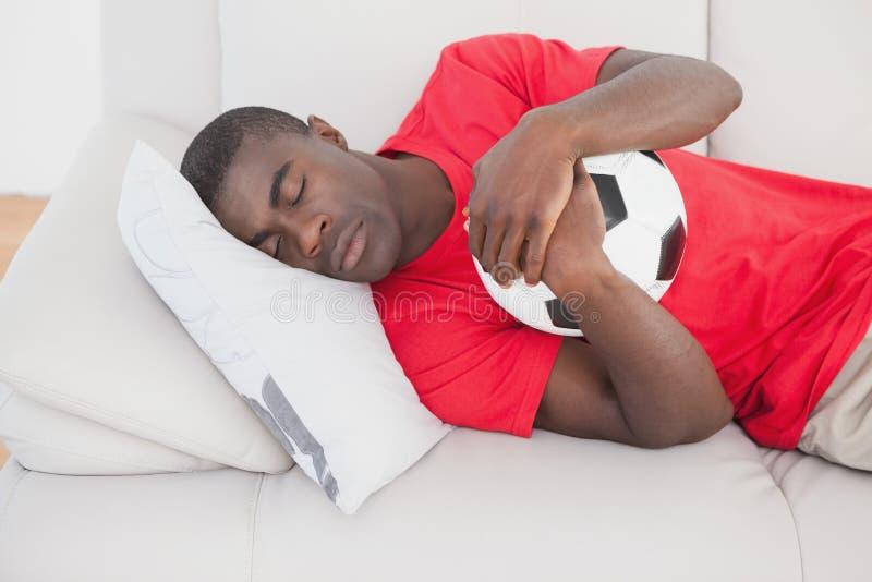 Ύπνος οπαδών ποδοσφαίρου στον καναπέ που αγκαλιάζει τη σφαίρα στοκ φωτογραφία