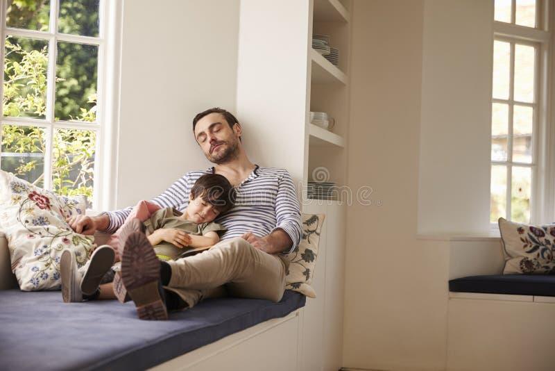 Ύπνος πατέρων και γιων στο κάθισμα παραθύρων στο σπίτι από κοινού στοκ εικόνες
