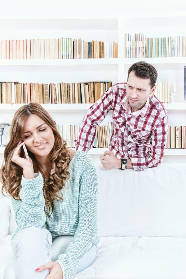 Ύποπτος άνδρας που εξετάζει τη γυναίκα του που μιλά στο τηλέφωνο στοκ φωτογραφίες
