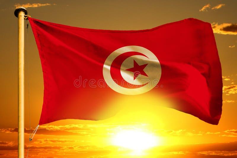 Ύφανση σημαιών της Τυνησίας στο όμορφο πορτοκαλί ηλιοβασίλεμα με το υπόβαθρο σύννεφων στοκ εικόνα με δικαίωμα ελεύθερης χρήσης