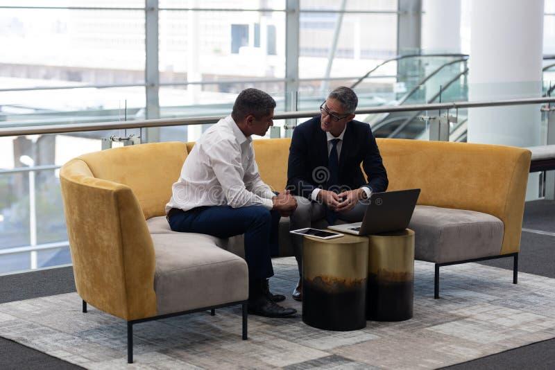 Ώριμα ανώτατα στελέχη επιχείρησης Καυκασίων που μιλούν το ένα με το άλλο στον καναπέ στοκ εικόνα με δικαίωμα ελεύθερης χρήσης