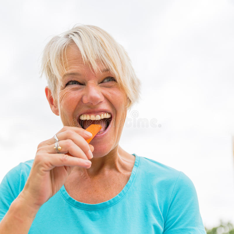 Ώριμα δαγκώματα γυναικών σε ένα καρότο στοκ φωτογραφία με δικαίωμα ελεύθερης χρήσης