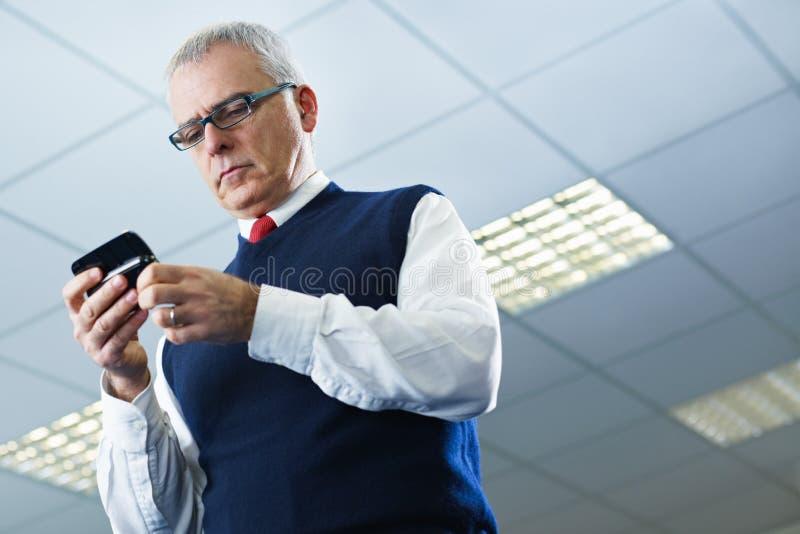 Ώριμα ηλεκτρονικά ταχυδρομεία ανάγνωσης επιχειρηματιών στο κινητό τηλέφωνο στοκ φωτογραφίες με δικαίωμα ελεύθερης χρήσης