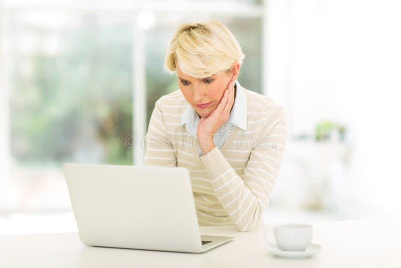 Ώριμα ηλεκτρονικά ταχυδρομεία ανάγνωσης γυναικών στοκ φωτογραφίες