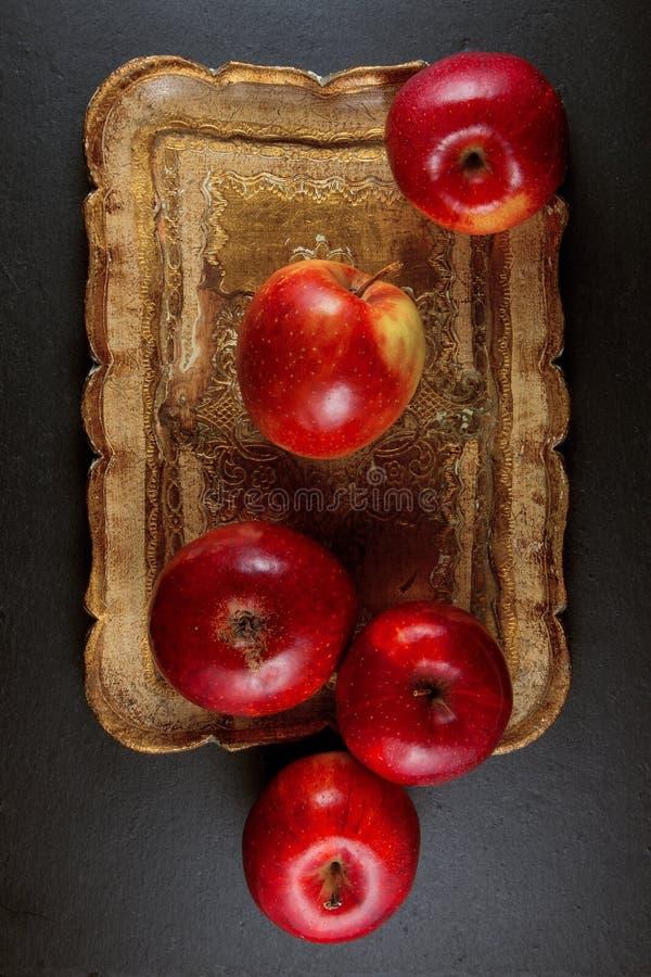 Ώριμα κόκκινα μήλα σε ένα ξύλινο κύπελλο σε ένα υπόβαθρο πιάτων πλακών στοκ φωτογραφία με δικαίωμα ελεύθερης χρήσης