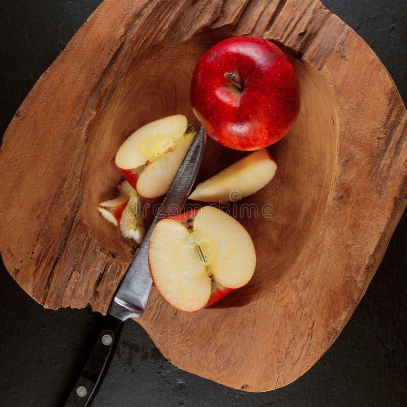 Ώριμα κόκκινα μήλα σε ένα ξύλινο κύπελλο σε ένα υπόβαθρο πιάτων πλακών στοκ εικόνες