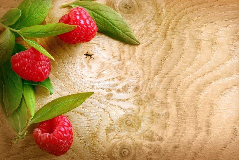 Ώριμα κόκκινα σμέουρα σε μια woodgrain σύσταση στοκ φωτογραφία με δικαίωμα ελεύθερης χρήσης