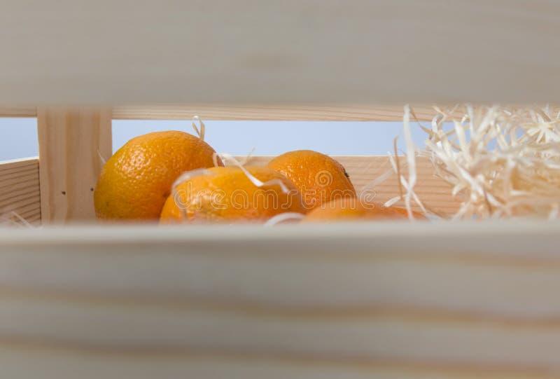 Ώριμα νόστιμα tangerines με τα φύλλα στο ξύλινο κιβώτιο στοκ φωτογραφία