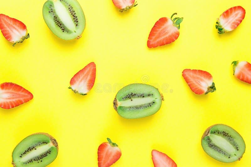 Ώριμα οργανικά διχοτομημένα φράουλες και ακτινίδια που διασκορπίζονται στο φωτεινό κίτρινο υπόβαθρο στο σχέδιο χρώματα δονούμενα στοκ εικόνα