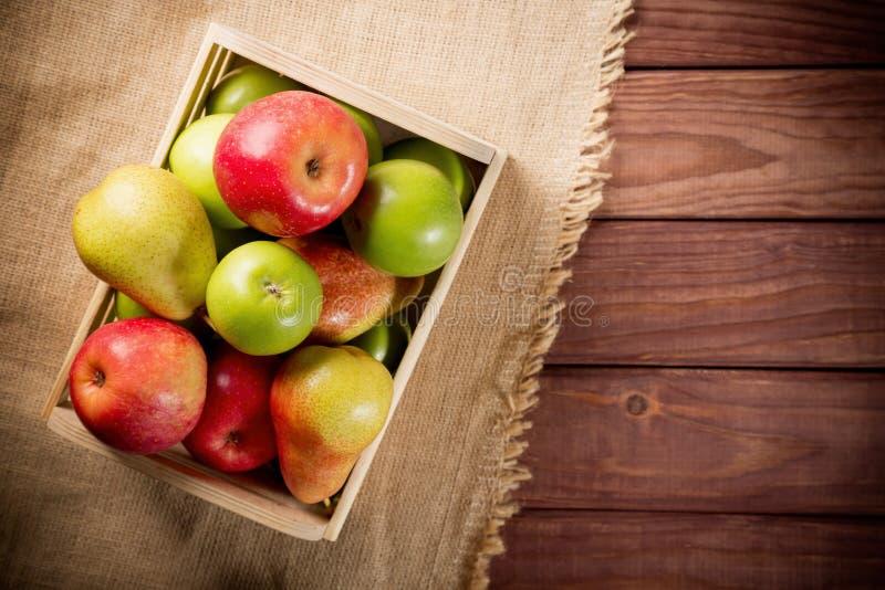 Ώριμα πράσινα και κόκκινα μήλα με τα αχλάδια σε ένα ξύλινο κιβώτιο sackcloth και το καφετί ξύλινο αγροτικό υπόβαθρο Εποχιακή εικό στοκ φωτογραφίες