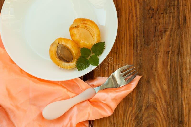 Ώριμα φρέσκα φρούτα βερίκοκων σε ένα άσπρο πιάτο στο ξύλινο υπόβαθρο Διαστημικά, delisious υγιή τρόφιμα αντιγράφων στοκ εικόνες με δικαίωμα ελεύθερης χρήσης