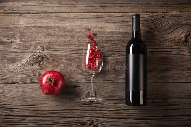 Ώριμα φρούτα ροδιών με ένα ποτήρι του κρασιού, ένα μπουκάλι σε ένα ξύλινο υπόβαθρο στοκ φωτογραφίες