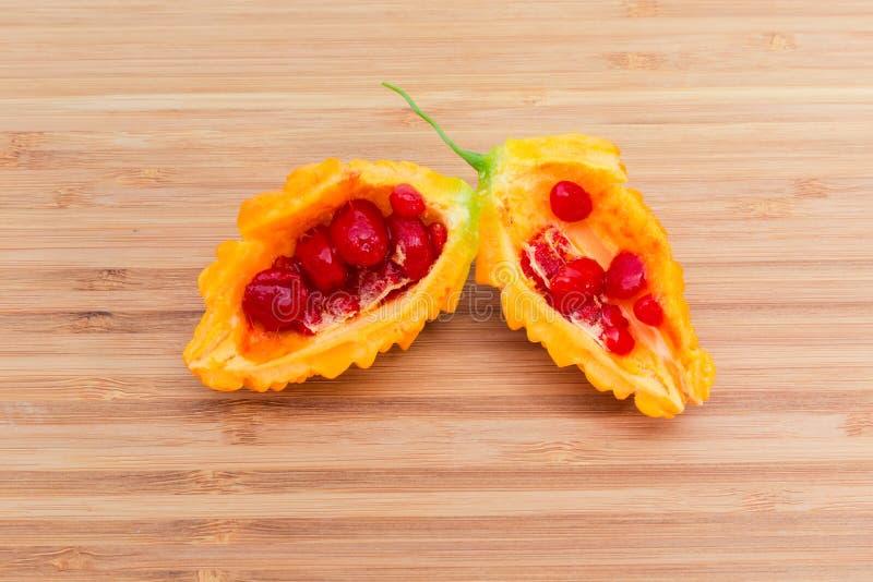 Ώριμα φρούτα του momordica που κόβονται στο μισό στην ξύλινη επιφάνεια στοκ εικόνα