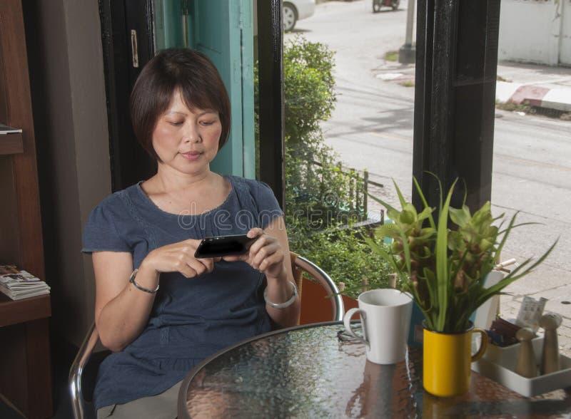 Ασιατική γυναίκα με το κινητό τηλέφωνο στοκ εικόνες