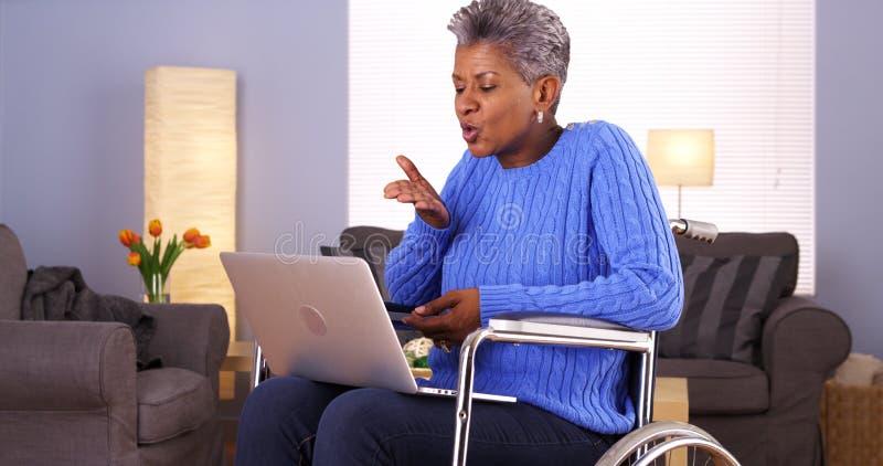 Ώριμη αφρικανική γυναίκα που μιλά με το φίλο στο lap-top στοκ εικόνες