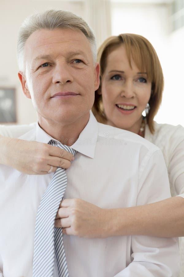 Ώριμη γραβάτα ρύθμισης γυναικών του επιχειρηματία στο σπίτι στοκ εικόνες