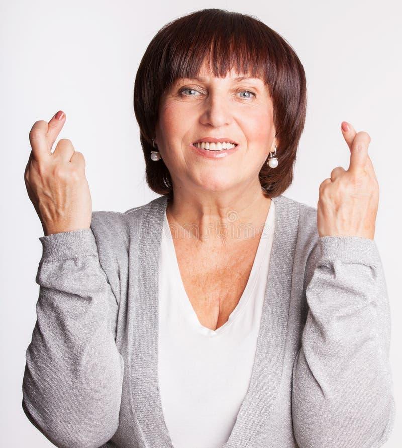 Ώριμη γυναίκα με τα διασχισμένα δάχτυλα στοκ φωτογραφία