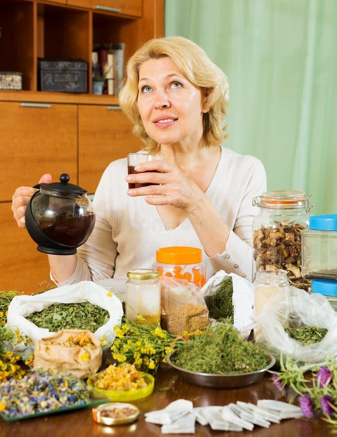 Ώριμη γυναίκα με τα ξηρά χορτάρια που παρασκευάζει το βοτανικό τσάι στοκ φωτογραφία