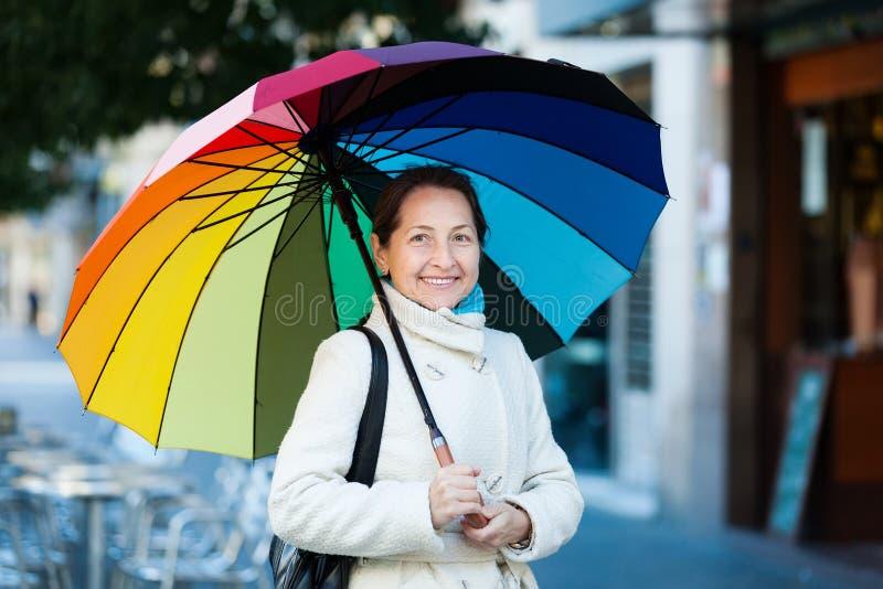 Ώριμη γυναίκα με την ομπρέλα το φθινόπωρο στοκ εικόνες