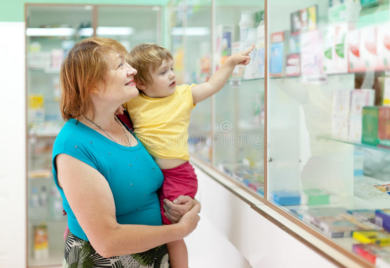 Ώριμη γυναίκα με το παιδί στο φαρμακείο στοκ εικόνα