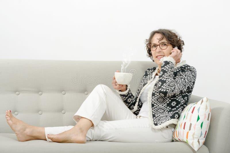 Ώριμη γυναίκα με το τηλέφωνο, τσάι κατανάλωσης στοκ εικόνα