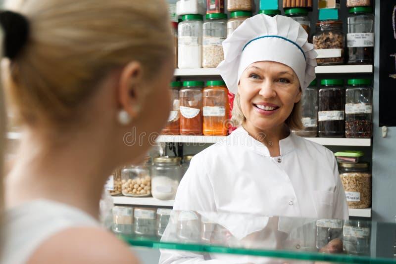 Ώριμη γυναίκα που αγοράζει τα διαφορετικά καρύδια στην τοπική υπεραγορά στοκ φωτογραφία με δικαίωμα ελεύθερης χρήσης