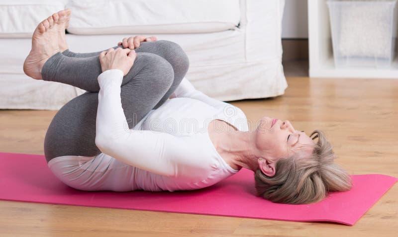 Ώριμη γυναίκα που ασκεί pilates στοκ εικόνες