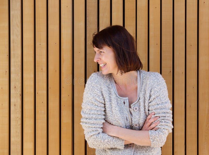 Ώριμη γυναίκα που γελά με τα όπλα που διασχίζονται στοκ φωτογραφία