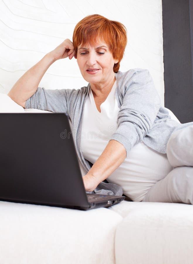 Ώριμη γυναίκα που εξετάζει το lap-top στοκ φωτογραφία