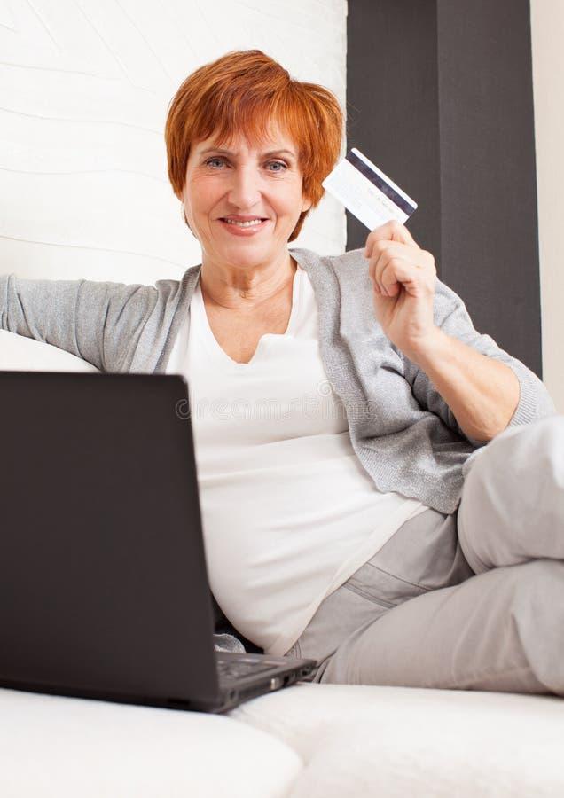 Ώριμη γυναίκα που εξετάζει το lap-top στοκ φωτογραφίες