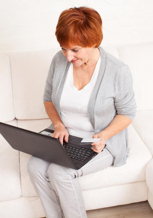 Ώριμη γυναίκα που εξετάζει το lap-top στοκ εικόνες