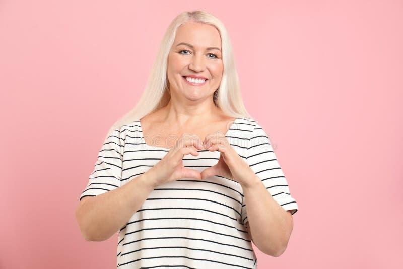 Ώριμη γυναίκα που κατασκευάζει την καρδιά με τα χέρια της στοκ εικόνα