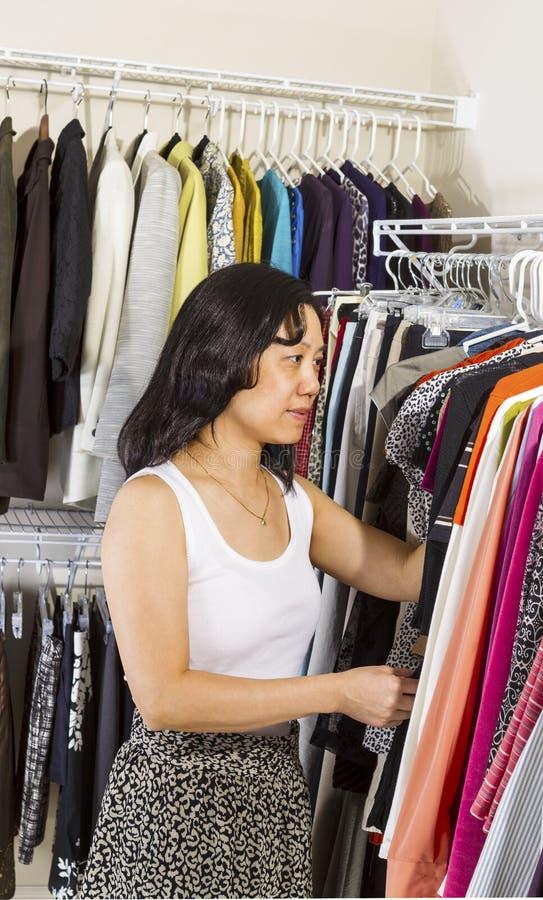Ώριμη γυναίκα που ντύνει μέσα στο εισαγώμενο ντουλάπι στοκ φωτογραφία