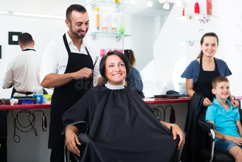 Ώριμη γυναίκα που παίρνει το hairdo του αρσενικού κομμωτή στοκ εικόνες με δικαίωμα ελεύθερης χρήσης