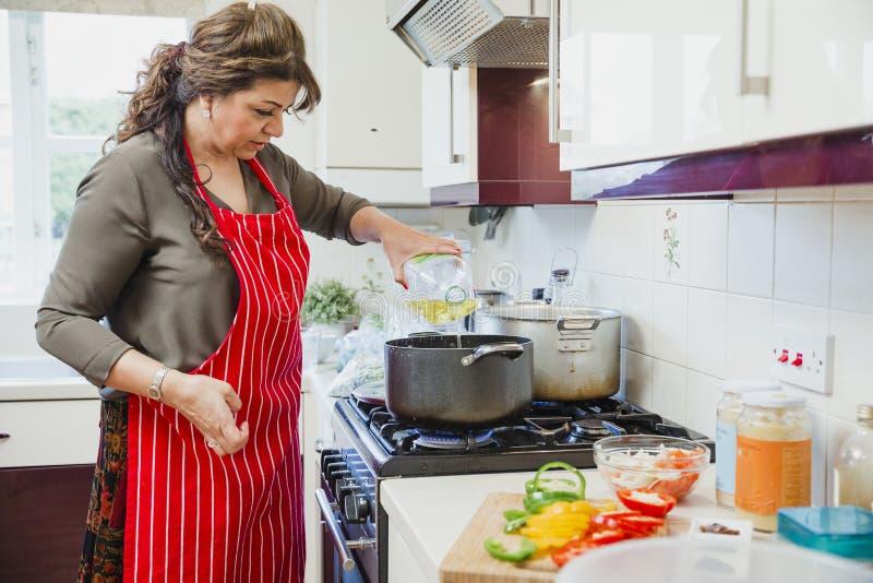 Ώριμη γυναίκα που προσθέτει το πετρέλαιο σε ένα τηγάνι στοκ φωτογραφία με δικαίωμα ελεύθερης χρήσης