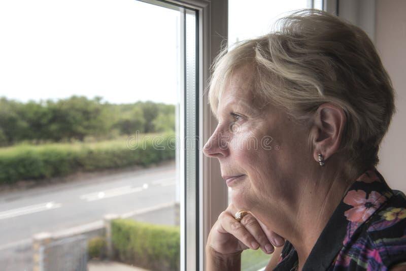 Ώριμη γυναίκα που σκέφτεται και που κοιτάζει από ένα παράθυρο στοκ φωτογραφίες με δικαίωμα ελεύθερης χρήσης