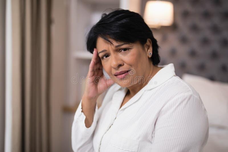 Ώριμη γυναίκα που υποφέρει με τον πονοκέφαλο στο σπίτι στοκ φωτογραφίες