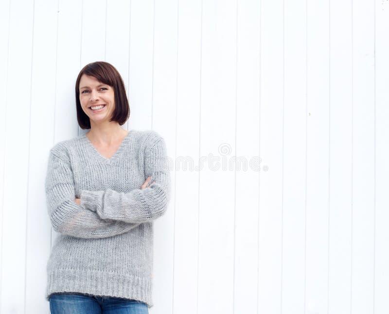 Ώριμη γυναίκα που χαμογελά ενάντια στον άσπρο τοίχο στοκ εικόνα με δικαίωμα ελεύθερης χρήσης