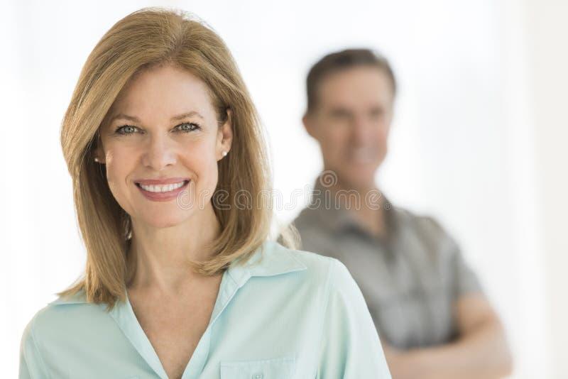 Ώριμη γυναίκα που χαμογελά με τον άνδρα που στέκεται στο υπόβαθρο στοκ εικόνες