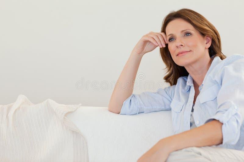 Ώριμη γυναίκα στις σκέψεις στον καναπέ στοκ φωτογραφία με δικαίωμα ελεύθερης χρήσης